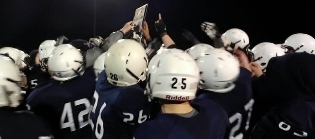 Mill Valley football players celebrate the team's newly won district trophy after Friday's 77-33 victory against Lansing.