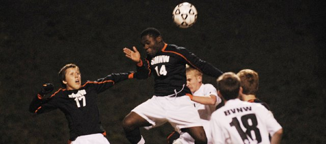 SMNW senior Junior Agbor (14) heads a corner kick with junior Hunter Thompson (17) nearby. The Cougars lost to Blue Valley Northwest, 1-0, in the final minute of overtime on Tuesday in state quarterfinal play.