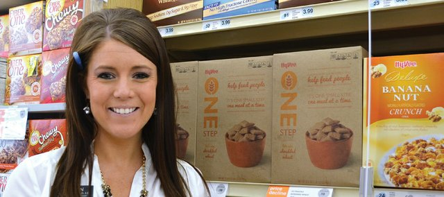 Megan Callahan, a registered dietitian with the Shawnee Hy-Vee store, is pictured in the cereal aisle, where a NuVal score of 91 is posted for Shredded Wheat with wheat and bran and score of 32 is posted for Lightly Frosted Shredded Wheat.