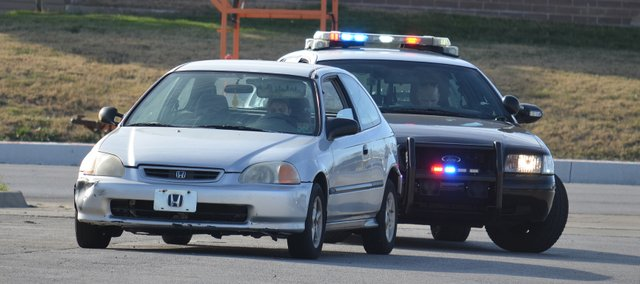 A Shawnee Police officer stops a motorist Friday in the parking lot of the Tomahawk Shopping Center at 75th Street and Nieman. Heightened police presence in the 75th Street corridor has been credited with reductions in crime and traffic accidents.