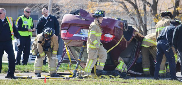 Shawnee firefighters work to free a 71-year-old woman from her overturned car following a wreck Wednesday morning at Shawnee Mission Parkway and Caenen Lake Road.