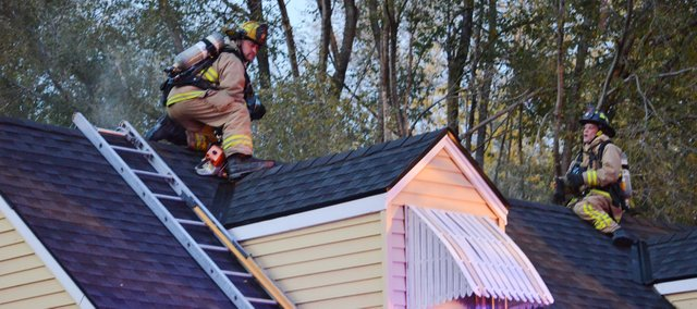 Capt. Jeff Salmon (left) and Firefighter Jack Dillon fought the Thursday evening house fire at 10430 W. 56th Terrace from the home's rooftop.