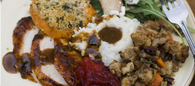 The turkey may be the centerpiece, but a classic Thanksgiving dinner simply isnt complete without a bevy of traditional sides. Pictured is a dinner plate of cider brined turkey with sage gravy, peach cranberry sauce, sour cream and chive mashed potatoes, sausage pecan stuffing, arugula pear salad with pomegranate vinaigrette and goat cheese and herb crusted sweet potatoes.