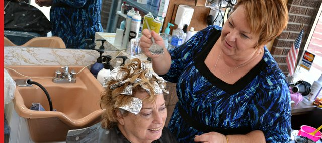 Martha Wright, owner of Whitney's Creative Hair Designs, styles and colors Sue Cranston's hair.