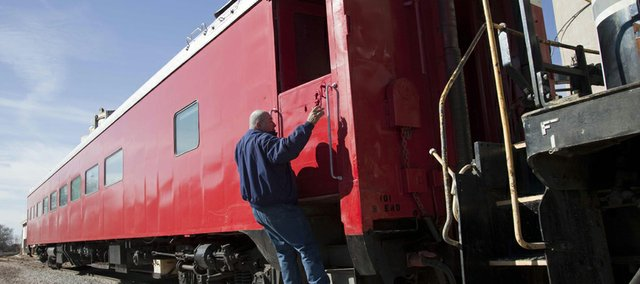 Ira Schreiber, a member of the Kansas Belle Dinner Train ownership team, climbs down Monday from the first of the business' dining cars to arrive at Midland Railway's Baldwin City yard. The owners hope to have the dinner train operating late this year.