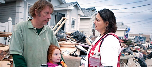 "Staten Island, N.y., resident Frank McDaniel and daughter, Isabel, receive a ""Sandy Kit"" during the aftermath of Superstorm Sandy from American Red Cross volunteer Marcella Baum."