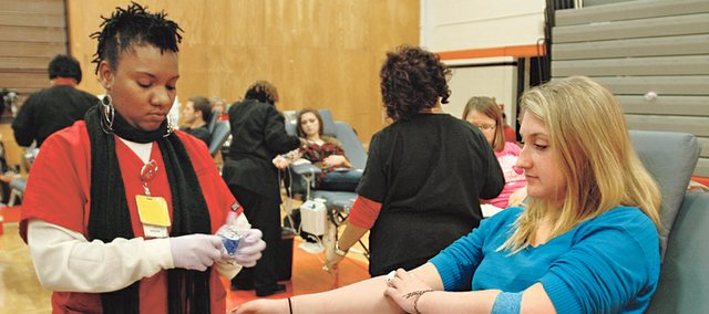 Rena Soller, Shawnee Mission Northwest senior, has just given a whole blood donation with the help of Community Blood Center phlebotomist Shayla Winston, left. The school's student council hosted its annual fall blood drive, in partnership with the blood center, Nov. 6.