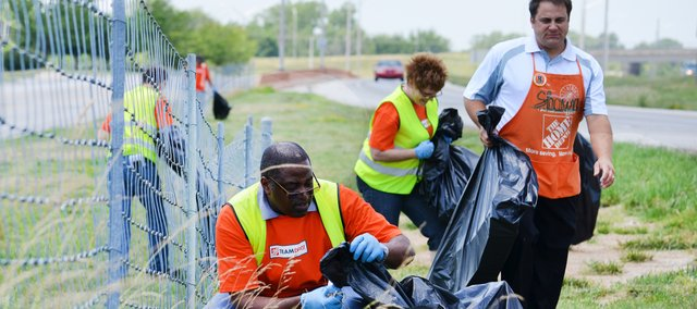 Andre Blanchette of Home Depot in Shawnee stoops to pick up litter as his district manager, Shawn Edwards, and fellow store employee Tammy Wood follow him down the Shawnee Mission Parkway frontage road between Lackman and Maurer roads during a cleanup effort last June. Eight Home Depot employees stepped forward to be the first participants in Shawnee's new Adopt-A-Spot beautification program.
