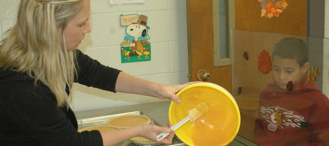 Kristen Moulin, left, pours pumpkin pie filling into a pie crust as Dexter Gilliam looks on Monday at the Edwardsville Elementary School cafeteria.