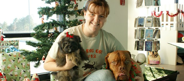 Amber Anderton, owner of Wagg'n Tails Day Spa, uses a couple of her dogs to model the Christmas apparel she offers.