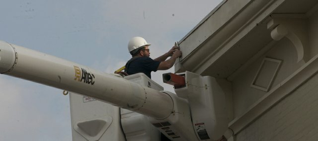 Baldwin City head lineman Chris Croucher puts new Christmas lights on a downtown storefront. The lights will be illuminated for the first time at Saturday's Festival of Lights.