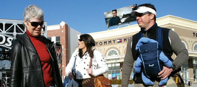 In this file photo, a family strolls and shops through the Legends Outlets Kansas City in Kansas City, Kan. Failure to take safety precautions while shopping this Christmas season can leave shoppers vulnerable to theft.
