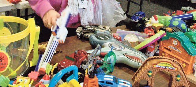 Neesha Caudill of Overland Park peruses the tables of free toys Saturday at GracePoint Church's annual Christmas toy drive.