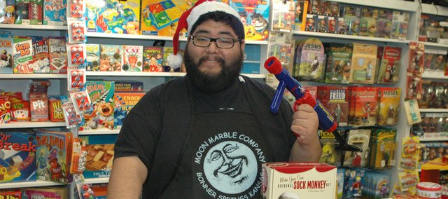 "Jay Reyes, employee at Moon Marble Co., displays some of the best sellers at the store, including (from left on the table) the Marshmallow Blaster, which Reyes also is holding; the Sock Monkey; the Dashboard Zombie; and the Mug Shots shot glasses. With a wide array of games and toys for both adults and children, not to mention blown glass items and marbles, Reyes helps a lot of customers finds gifts. ""Whether you've been naughty or nice, we've got you covered,"" Reyes said."