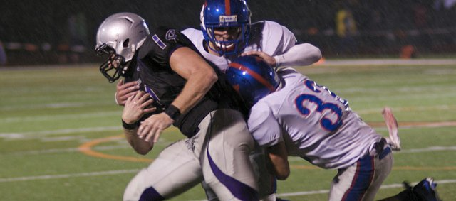Baldwin senior Dayton Valentine drags to Wellsville defenders downfield after catching a pass in the Bulldogs' season opener. 