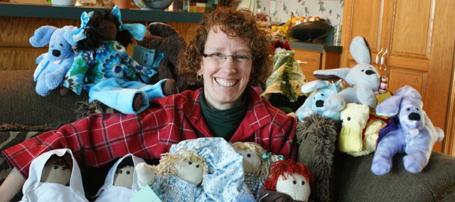 Christine Henderson, owner of Jacob's Toy Box, takes a break with some of the stuffed dogs, ducks and dolls she sells.