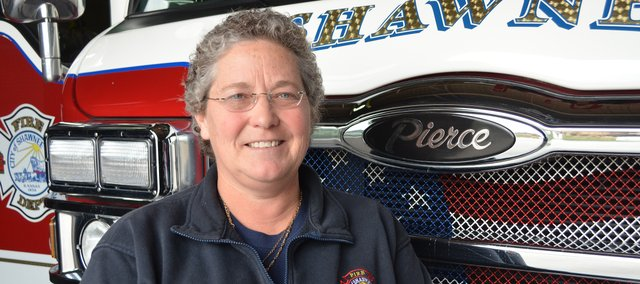 Capt. Joan Moore, pictured with a fire truck at the Shawnee Fire Department's headquarters station, is retiring this week after a long firefighting career.
