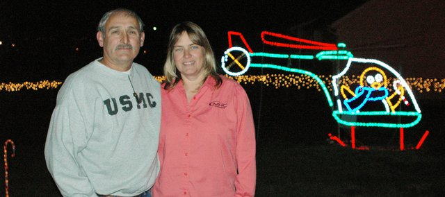 "Buddy (left) and Sharon Green stand in front of one of the most popular elements of their light display, a penguin inside a helicopter. ""I'm not sure what that has to do with Christmas,"" Buddy says, but ""man, everybody loves it."""