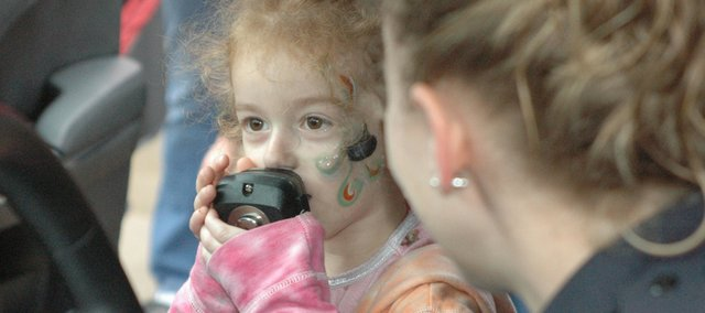 Haley Bernard, 4, of Bonner Springs holds the handset for the public announcement system in a Bonner Springs Police Department patrol, with the help of Officer Heather Pate Saturday at the Fire/EMS Station Open House. Visitors were able to learn how officers control the car's lights, horns and radio.