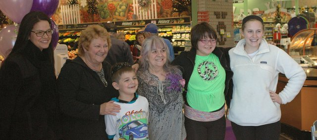 Gloria White, center, poses for a photo with several members of the Nolting family, who formerly owned the Bonner Springs Price Chopper store, Friday at her retirement party. White has worked at the story since 1981 and was known for her friendly demeanor and purple-streaked hair.
