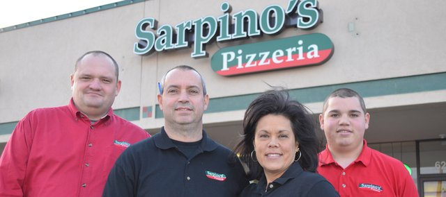 Steve and Cathy Darpel, center, owners of the new Sarpino's Pizzeria in Shawnee, are flanked by Vasili Bykau, far left, a trainer from Sarpino's Pizzeria's corporate office in Chicago, and the Darpels' son, Matt, who works at the new restaurant.