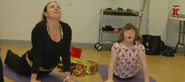 Tierney Thompson, left, and Cece Williams stretch during the Dec. 12 Zen Friends yoga class at the Bonner Springs Family YMCA. Cece is a student in Thompson's special education class at Bonner Springs Elementary School. Thompson taught her students yoga last year and said it helped them learn self-confidence and focus.