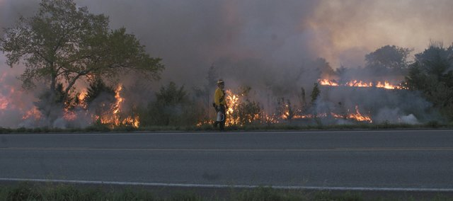 With plenty of fuel from drought conditions, a wildfire burns along U.S. Highway 56 as a  fireman walks along the highway. Firefighters from multiple departments fought three fires July 15 along the highway on the west edge of Baldwin City. The summer heat wave and drought, which persists, was the No. 2 local story of 2012.