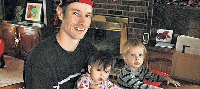 After two layoffs, Brian Bolen of Shawnee is working on earning a degree online through Johnson County Community College. He is also a stay-at-home father of 2-year-old Daniel, right, and 11-month-old Coleen.