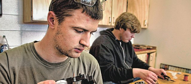 Lawrence High School engineering students Michael Latham, left, and Jacob Magauson team up Friday on a robotics project for a competition at Johnson County Community College. Lawrence school officials hope to form partnerships with three area community colleges to share space and offer training programs in Lawrence as part of a bond issue on the ballot this spring.