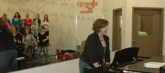 Christy Elsner, founder and director of Allegro choirs, runs through warm-ups with singers (seen in the mirror at rear) in Allegro Con Moto, the ensemble for girls grades six through 12, Monday at the choirs new permanent facilities at 228 Oak Street in Bonner Springs. Opening their new home was a highlight of the year along with a performance Dec. 3 at the White House.
