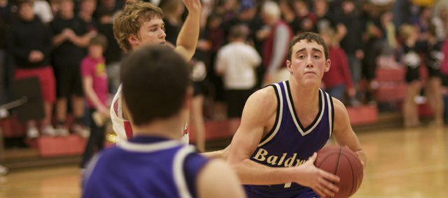 Bulldog Junior Luke Fursman looks for an open teammate Tuesday in Baldwins loss at Ottawa. The boys split their first two games after returning from the holiday break, beating Louisburg on Friday at home.