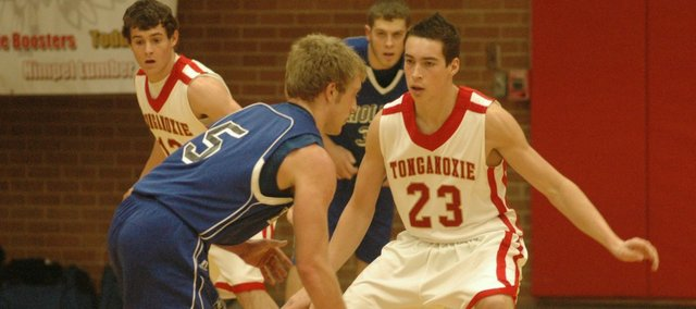 Ben Johnson plays defense against Holton's Tyler Burdiek. The Chieftains lost to the Wildcats, 71-56.
