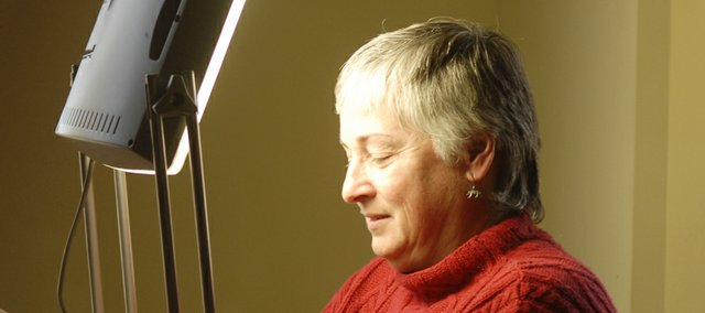 In this file photo, Becky Foerschler of Lawrence, who has seasonal affective disorder, reads by a SAD therapy light. The mood disorder affects more than 10 million Americans every year.