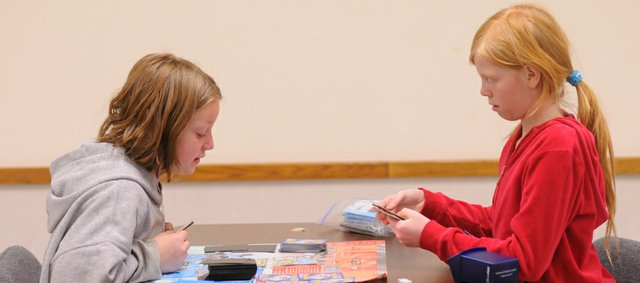 Isabelle Parks, 9, and Shelby Crum, 10, share a Pokémon battle Saturday afternoon at the Pokémon league at the Baldwin City Library. It was a big day for Crum, who won her first game in the league.