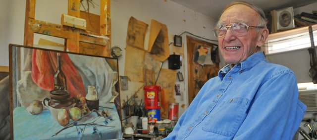 Tom Russell sits in front of an easel in a studio in his Baldwin City home. The 95-year-old former head of the Baker University art department, works in the studio daily. Russell will be honored Sunday at the annual chocolate. He and his late wife, Alice Anne, brought the auction, which now benefits the Lumberyard Arts Center, to Baldwin City 25 years ago after witnessing a similar event in South Dakota.