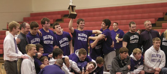 The Baldwin High School wrestling team hold high the first-place trophy it won with a 6-0 record in the Frontier League meet.