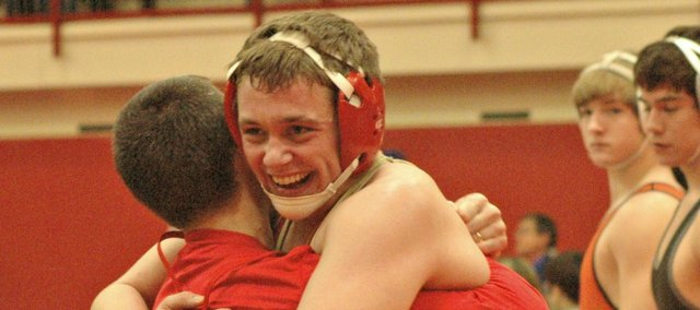 Tonganoxie High senior Gus Dent gets a hug from coach Jeremy Goebel after qualifying for the Class 4A state tournament on Saturday.