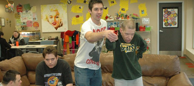 Staff member Kyler Paine, center, helps client Skip Henderson of Basehor play Wii Bowling Monday at Advocacy First in Bonner Springs, as Mark Huntington, left, looks on.