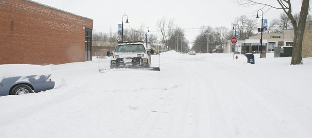A Baldwin City Public Works truck plows Seventh Street after snow quit falling late Tuesday morning.