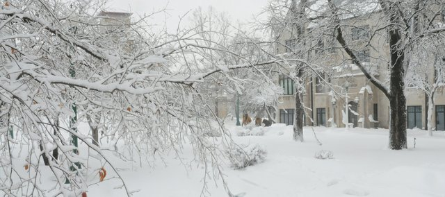 Baker University employees Tuesday clear campus sidewalks of snow. The university called off classes for the day, as it had during Thursday's blizzard. Tuesday's heavy snow made for beautiful landscapes but caused power outages snow-ladened tree limbs downed power lines