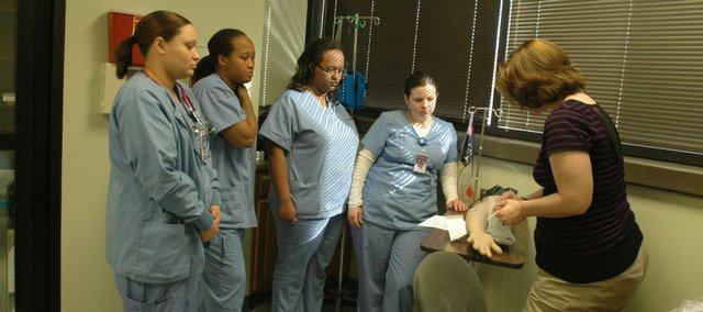 Kansas City Kansas Community College nursing instructor Teri Schwager, right, shows fourth-semester nursing students how to insert an IV in the nursing department's new simulation lab, built last semester. Students pictured from left to right are Erin Hysten of Kasnas City, Kan., Starla Union of Kansas City, Kan., Meskerem Ayele of Shawnee and Jessica Franz of Kansas City, Kan.