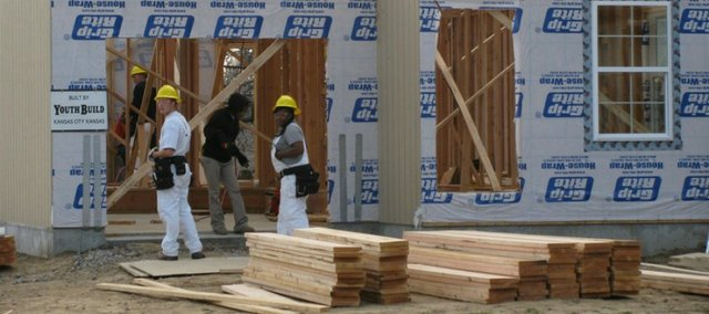 Volunteer workers help with the construction of new homes on Quindaro Boulevard, part of the Unified Government&#39;s effort to eliminate abandoned, foreclosed and tax delinquent property. The three-bedroom, two-bath houses with basements are listed at $120,000 each.  