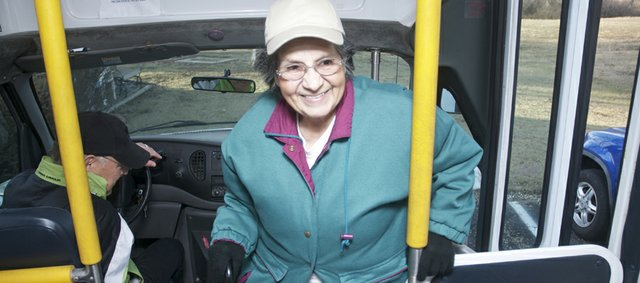 Lorettamay Davis enters the senior bus Tuesday to sit behind volunteer driver Bill Clement. Davis takes the bus twice weekly to Lawrence for hydrotherapy treatments for her arthritis. The bus has been in service since June providing rides to medical appoints and other places to the community's seniors 60 years of age or older.