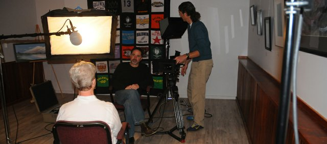 In April 2011, Doug Stremel, creative director of Gizmo Pictures, interviews Paula Johnson about her role in bringing a Smithsonian Institute traveling exhibit to Baldwin City's Lumberyard Arts Center while Gizmo producer Keith Walburg video tapes her remarks. Johnson is one of coordinators of the show at the Lumberyard, which opens Saturday.