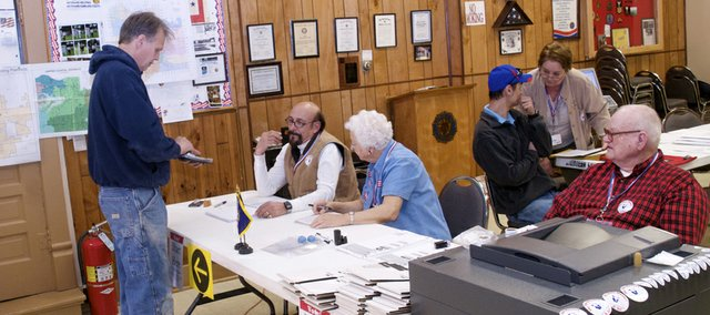 Shane Venable shows his identification as he readies to vote at the American Legion post as Braden Lorenz, in blue cap to the right, talks with precinct supervisor Kathy Davis about a provisional ballot. An even 200 of the precinct's 1,351 registered voters cast ballots Tuesday at the site.