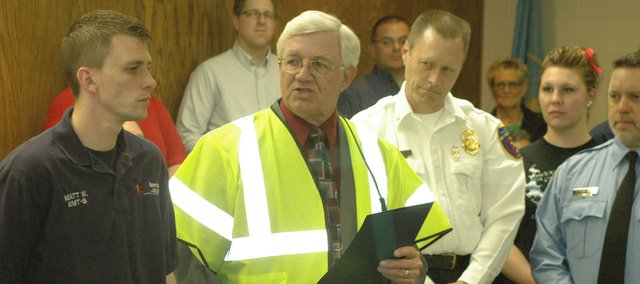 Wearing a vest to show his support for Work Zone Awareness Week, Smith reads a proclamation for National Volunteer Week, surrounded by dozens of the city's volunteers, at the April 8 city council meeting.