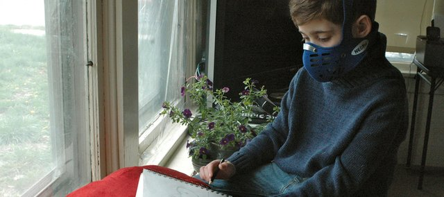 Quenten Hayes, wearing the mask that helps prevent him from inhaling germs, pauses as he draws a bird he can see from his living room window. Quenten is currently quarantined to his Bonner Springs home as his body fights an immunodeficiency syndrome and other illnesses.