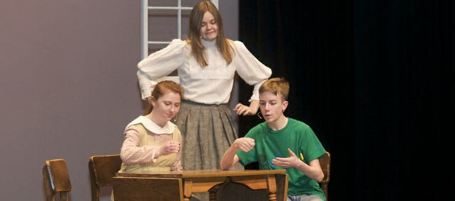 "Audrey Osborn (standing), Sammie Weiss and Drew Cheek portray members of the Webb family going about their morning routine in a scene from Thornton Wilder's classic ""Our Town."" Baldwin High School will perform the play a 7 p.m. Friday and Saturday at the Performing Arts Center."