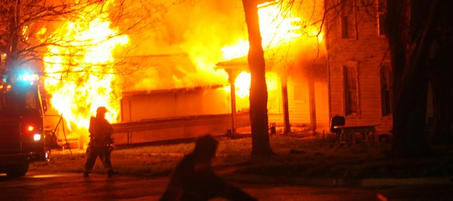 A Baldwin City fireman turns on a hydrant at the corner of Ninth and High streets as flames engulf a home on the southwest corner of the intersection. The fire broke out about 1:30 a.m. Saturday.