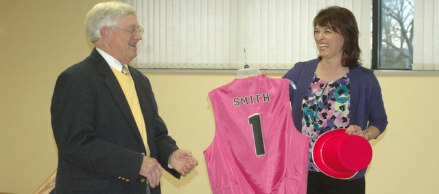 Marcia Harrington, right, presents retiring Mayor Clausie Smith with the pink top hat and vest commemorating his participation in the Marble Day Wacky Parade Monday at his retirement reception.